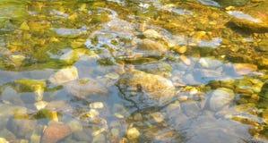 Οι κυματισμοί του νερού ξεκαθάρων απεικονίζουν το φως στο γλυκό νερό πέρα από τα χαλίκια και τις πέτρες στον καταρράκτη στην Ταϊλ στοκ εικόνες