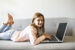 Οι κυματωγές μικρών κοριτσιών στο διαδίκτυο βάζουν στον καναπέ στοκ φωτογραφίες με δικαίωμα ελεύθερης χρήσης