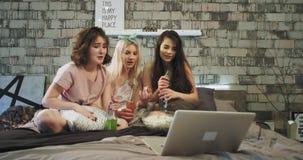 Οι κυρίες εφήβων φίλων κτηνών έχουν ένα κόμμα sleepover, στο κρεβάτι προσέχουν μια κωμωδία στο σημειωματάριο, χαμογελώντας και απόθεμα βίντεο