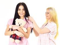 Οι κυρίες στα πρόσωπα χαμόγελου με το παιχνίδι βελούδου αντέχουν το βλέμμα χαριτωμένο Κοριτσίστικη έννοια ελεύθερου χρόνου Αδελφέ Στοκ φωτογραφία με δικαίωμα ελεύθερης χρήσης
