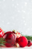 Οι κόκκινα διακοσμήσεις και το χριστουγεννιάτικο δέντρο ακτινοβολούν επάνω υπόβαθρο διακοπών Κάρτα Χαρούμενα Χριστούγεννας Στοκ Φωτογραφίες