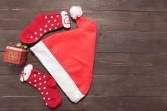 Οι κόκκινα κάλτσες, το καπέλο και το δώρο είναι στο ξύλινο υπόβαθρο με κενό Στοκ Φωτογραφίες