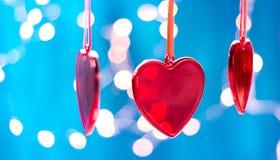 Οι κόκκινες διακοσμήσεις Χριστουγέννων, καρδιά και σφαίρα, ακτινοβολούν επάνω bokeh υπόβαθρο με αστράφτουν φω'τα Κάρτα Χαρούμενα  στοκ εικόνες