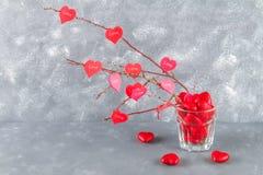 Οι κόκκινες καρδιές με μια αγάπη επιγραφής κρεμούν στους κλάδους σε ένα γκρίζο συγκεκριμένο υπόβαθρο απομονωμένο διάφορο διάνυσμα Στοκ Φωτογραφία