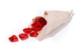 Οι κόκκινες καρδιές γυαλιού χύνονται έξω από ένα δέμα εγγράφου Στοκ φωτογραφίες με δικαίωμα ελεύθερης χρήσης