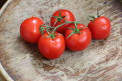 Οι κόκκινες ντομάτες σε έναν πράσινο κλάδο βρίσκονται σε έναν ξύλινο πίνακα Στοκ Εικόνες