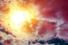 Οι κόκκινες, πορτοκαλιές και κόκκινες ακτίνες ήλιων κοιτάζουν μέσω των σύννεφων σωρειτών Στοκ Εικόνες