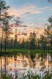 Οι κόκκινοι ουρανοί ηλιοβασιλέματος με τις αντανακλάσεις νερού στα σιβηρικά έλη και ένα τρυπώντας με τρυπάνι πετρέλαιο προσγειώνο Στοκ φωτογραφία με δικαίωμα ελεύθερης χρήσης