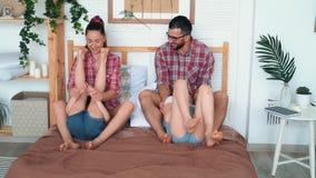 Οι κόρες γαργαλήματος γονέων, κάθονται στο κρεβάτι, γελούν και έχουν τον καλό χρόνο, ευτυχής οικογένεια απόθεμα βίντεο
