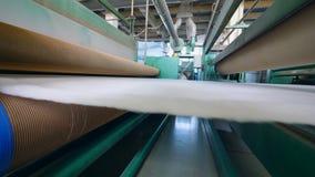 Οι κύλινδροι εργοστασίων κινούν ένα στρώμα του άσπρου συνθετικού υφάσματος απόθεμα βίντεο