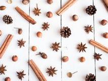 Οι κώνοι έλατου αστεριών καρυκευμάτων ραβδιών κανέλας στο άσπρο ξύλινο επίπεδο υποβάθρου βρέθηκαν Στοκ εικόνα με δικαίωμα ελεύθερης χρήσης