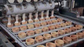 Οι κώνοι παγωτού με το παγωτό από η μηχανή που γεμίζουν Κινηματογράφηση σε πρώτο πλάνο HD απόθεμα βίντεο