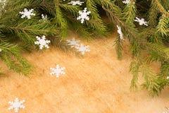 Οι κλάδοι των χριστουγεννιάτικων δέντρων στο υπόβαθρο των ξύλινοι πινάκων και snowflakes Στοκ Εικόνες