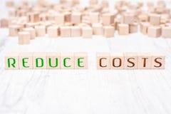 Οι λέξεις μειώνουν τις δαπάνες που διαμορφώνονται από τους ξύλινους φραγμούς σε έναν άσπρο πίνακα στοκ εικόνα