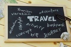 Οι λέξεις ταξιδιού καλύπτουν γραπτός στο μαύρο πίνακα με τους χάρτες, τα θεάματα και το τσαλακωμένο έγγραφο Στοκ Εικόνες