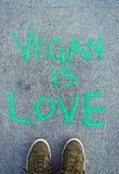 Οι λέξεις Vegan είναι αγάπη στην πράσινη εγγραφή κιμωλίας στο πεζοδρόμιο τσιμέντου στοκ εικόνες