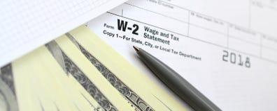 Οι λογαριασμοί μανδρών, σημειωματάριων και δολαρίων είναι ψέματα στη φορολογική μορφή W-2 W στοκ εικόνες