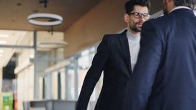 Οι μέσης ηλικίας επιχειρηματίες που συναντιούνται στο τίναγμα καφέδων δίνουν το χαιρετισμό ομιλίας απόθεμα βίντεο