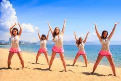 Οι μαζορέτες χορεύουν στην παραλία με τα χέρια προς τα πάνω ενάντια στην κυανή θάλασσα Στοκ εικόνα με δικαίωμα ελεύθερης χρήσης