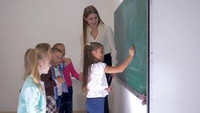 Οι μαθητές και ο δάσκαλος που στέκονται κοντά whiteboard στην τάξη, μαθήτρια παίρνουν το κομμάτι της κιμωλίας και γράφουν την απά απόθεμα βίντεο