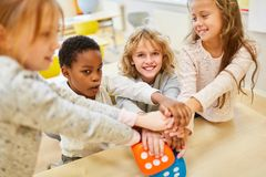 Οι μαθητές συσσωρεύουν τα χέρια για την ολοκλήρωση στοκ φωτογραφία
