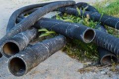 Οι μακριοί μαύροι σωλήνες με το εξωτερικό νήμα βρίσκονται στην άμμο Στοκ Εικόνα