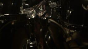 Οι μακρυμάλλεις τυμπανιστές παίζουν την εξάρτηση τυμπάνων σε ένα σκοτεινό δωμάτιο σε ένα μαύρο υπόβαθρο λευκό βράχου μουσικών ατό απόθεμα βίντεο