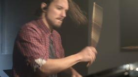 Οι μακρυμάλλεις τυμπανιστές παίζουν την εξάρτηση τυμπάνων σε ένα σκοτεινό δωμάτιο σε ένα μαύρο υπόβαθρο λευκό βράχου μουσικών ατό φιλμ μικρού μήκους