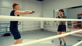 Οι μαχητές θερμαίνουν πρίν εκπαιδεύουν στη θέση κοντά στο ριγκ στη γυμναστική Έννοια επαγγελματικών αθλημάτων φιλμ μικρού μήκους