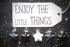 Οι μαύρες σφαίρες Χριστουγέννων, Snowflakes, απόσπασμα απολαμβάνουν τα μικρά πράγματα Στοκ φωτογραφία με δικαίωμα ελεύθερης χρήσης