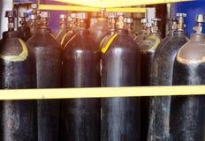 Οι μαύροι κύλινδροι με το οξυγόνο είναι στο εργοστάσιο στο κατάστημα, ένα ηλιοβασίλεμα σπάζει μέσω του παραθύρου, μπαλόνι στοκ εικόνες