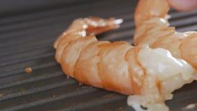 Οι μεγάλες γαρίδες ψήνονται στη σχάρα σε ένα τηγάνι Το χέρι μαγείρων βάζει και γυρίζει τις γαρίδες στο τηγάνι απόθεμα βίντεο