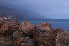 Οι μεγάλες πέτρες σχεδιάζονται για να προστατεύσουν την ακτή από τα μεγάλα κύματα Η υδρονέφωση πρωινού κατεβαίνει από το βουνό Στοκ εικόνες με δικαίωμα ελεύθερης χρήσης