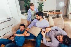 Οι μεθυσμένοι τύποι κοιμούνται αφότου θέτουν τα γεγονότα νύχτας στο πάτωμα και τον καναπέ σε διαφορετικό στο καθιστικό στοκ φωτογραφίες με δικαίωμα ελεύθερης χρήσης