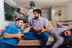Οι μεθυσμένοι τύποι κοιμούνται αφότου θέτουν τα γεγονότα νύχτας στο πάτωμα και τον καναπέ σε διαφορετικό στο καθιστικό στοκ εικόνα με δικαίωμα ελεύθερης χρήσης