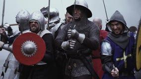 Οι μεσαιωνικοί στρατιώτες με τις ασπίδες και τα ξίφη στέκονται στο καπνώές πεδίο μάχη απόθεμα βίντεο