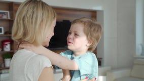 Οι μητέρες δίνουν στοργικά να κρατήσουν το πηγούνι του μικρού χαμογελώντας όμορφου αγοριού που παρουσιάζει άσπρα αστεία δόντια πα φιλμ μικρού μήκους