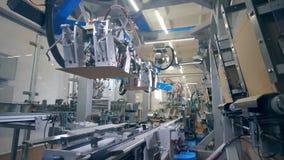 Οι μηχανές εργοστασίων συνδέουν τα μέρη των κουτιών από χαρτόνι σε μια γραμμή φιλμ μικρού μήκους
