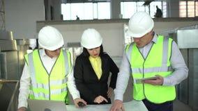 Οι μηχανικοί ανδρών και γυναικών έχουν τη συνομιλία και να φανούν συνολικά σχεδιάγραμμα Οι αρσενικοί και θηλυκοί διευθυντές αποθη απόθεμα βίντεο