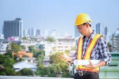 Οι μηχανικοί ατόμων στέκονται στα ψηλά κτίρια και τη συζήτηση για τα τηλέφωνα κυττάρων Στοκ Φωτογραφίες