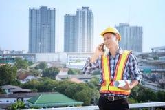 Οι μηχανικοί ατόμων στέκονται στα ψηλά κτίρια και τη συζήτηση για τα τηλέφωνα κυττάρων Στοκ Εικόνες