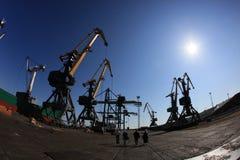 Οι μηχανικοί πηγαίνουν μεταξύ των γερανών ατσάλινων σκελετών στο θαλάσσιο λιμένα στοκ εικόνες με δικαίωμα ελεύθερης χρήσης