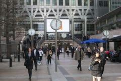 Οι μη αναγνωρισμένοι άνθρωποι στο Canary Wharf περπατούν μεταξύ των ρολογιών Έξι δημόσια ρολόγια από το Konstantin Grcic σχεδιάστ Στοκ φωτογραφία με δικαίωμα ελεύθερης χρήσης