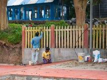Οι μη αναγνωρισμένοι ζωγράφοι απασχολούνται σε έναν τοίχο στο σταθμό τρένου Ooty στοκ εικόνα