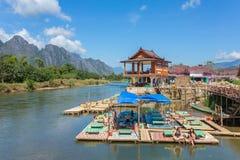 Οι μη αναγνωρισμένοι τουρίστες στηρίζονται στο εστιατόριο riverfront σε Vang Vieng, Λάος Στοκ Φωτογραφίες