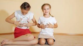 Οι μικρές αδελφές που κάθονται στο πάτωμα και χρωματίζουν μια μπλούζα με τα χέρια τους στοκ φωτογραφία με δικαίωμα ελεύθερης χρήσης