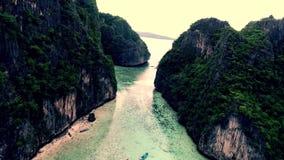 Οι μικρές βάρκες τουριστών στο τυρκουάζ μπλε ήρεμο ωκεάνιο νερό που περιβάλλεται από την τεράστια τροπική πέτρα λικνίζουν το δάσο απόθεμα βίντεο
