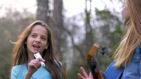 Οι μικρές φίλες έχουν τη διασκέδαση στην ημέρα άνοιξη πάρκων παίξτε τον ανόητο τραγουδά την κιθάρα μαζί παιχνιδιού τραγουδιών χορ απόθεμα βίντεο
