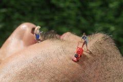 Οι μικροί άνθρωποι που κόβουν την τρίχα από το α επανδρώνουν το πρόσωπο Στοκ Φωτογραφία