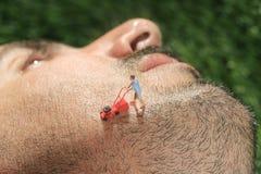 Οι μικροί άνθρωποι που κόβουν την τρίχα από το α επανδρώνουν το πρόσωπο Στοκ φωτογραφία με δικαίωμα ελεύθερης χρήσης
